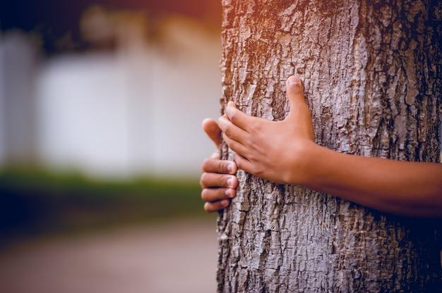 La photo a embrassé les arbres de jeunes hommes qui aiment la nature. concept de soins naturels