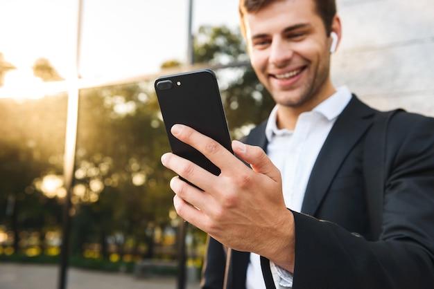 Photo d'un employé de bureau en costume tenant un téléphone mobile, tout en se tenant à l'extérieur contre le bâtiment