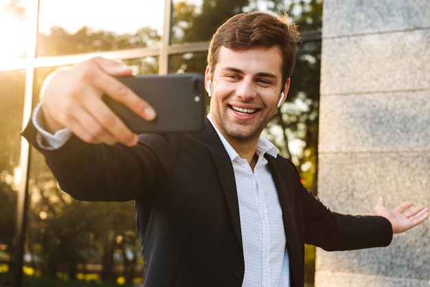 Photo d'un employé de bureau souriant en costume tenant un téléphone mobile pour selfie, tout en se tenant à l'extérieur contre le bâtiment