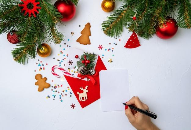 Photo d'enveloppe de noël rouge, biscuits, mains avec stylo, branches de décorations de noël d'épinette sur blanc vide