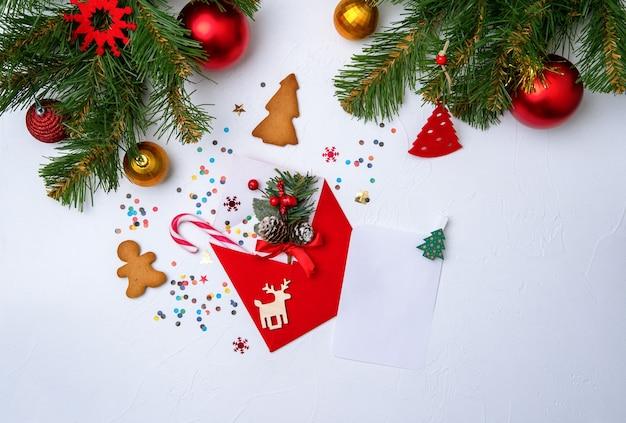 Photo d'enveloppe rouge, biscuits, branches de décorations de noël d'épinette sur blanc vide