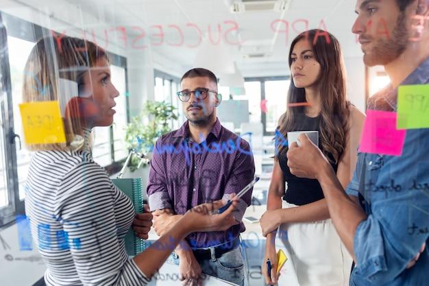 Photo d'une équipe commerciale prospère discutant ensemble devant le panneau de verre du bureau dans l'espace de coworking.