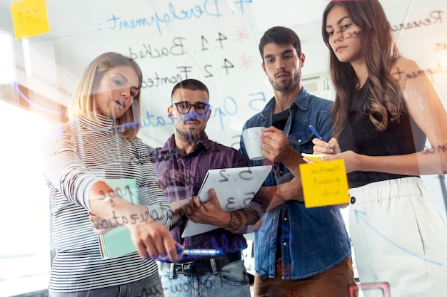 Photo d'une équipe commerciale prospère écrivant sur des autocollants sur un panneau de verre de bureau tout en discutant ensemble dans l'espace de coworking.
