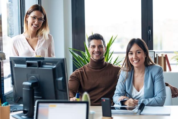 Photo d'une équipe de jeunes entreprises prospères debout autour d'un ordinateur tout en regardant la caméra dans l'espace de coworking.