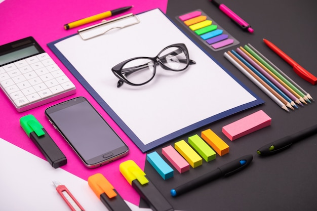 Photo de l'espace artistique moderne avec presse-papiers, lunettes, papeterie et smartphone sur rose et noir.