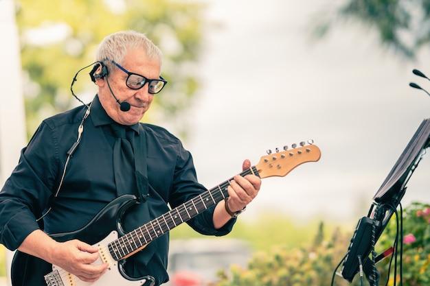 Photo avec espace de copie d'un vieux musicien jouant de la guitare électrique à l'extérieur