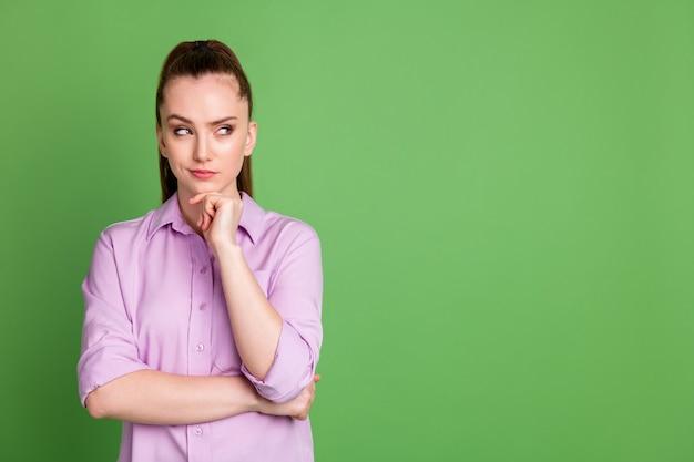 Photo d'esprit smart girl touch hand chin look copyspace pense choix de décision pensées porter chemise violette isolée sur fond de couleur verte
