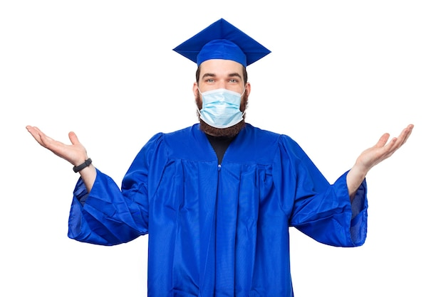 Photo d'un étudiant confus portant chapeau et baccalauréat et portant un masque facial