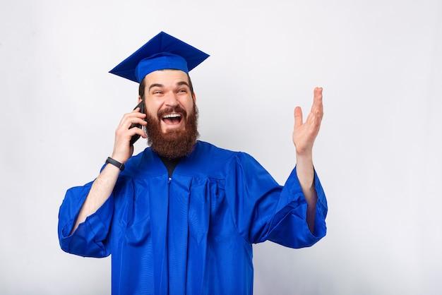 Photo d'un étudiant étonné en robe bleue célibataire parlant sur smartphone