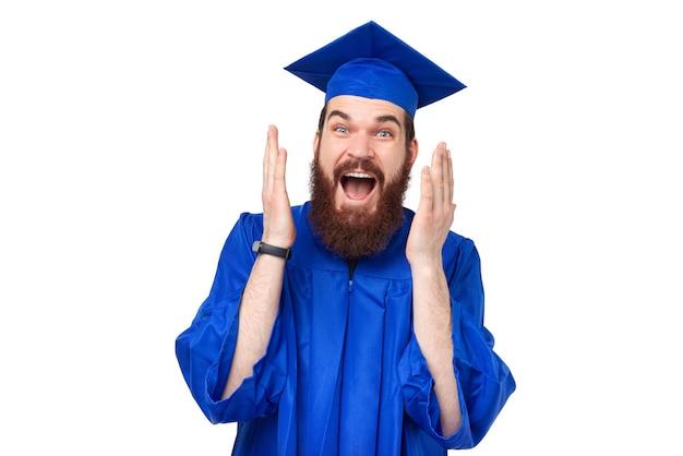 Photo d'un étudiant surpris avec barbe portant une robe bleue et faisant des gestes