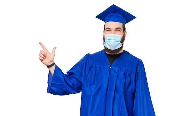 Photo d'un étudiant en tenue de célibataire et bonnet de graduation pointant vers l'extérieur tout en portant un masque facial