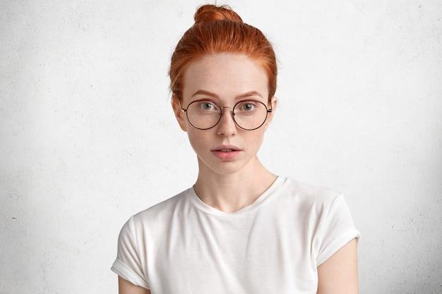Photo d'étudiante rousse intelligente sérieuse avec noeud de cheveux roux, porte des lunettes rondes, vient en conférence à l'université, isolé sur blanc