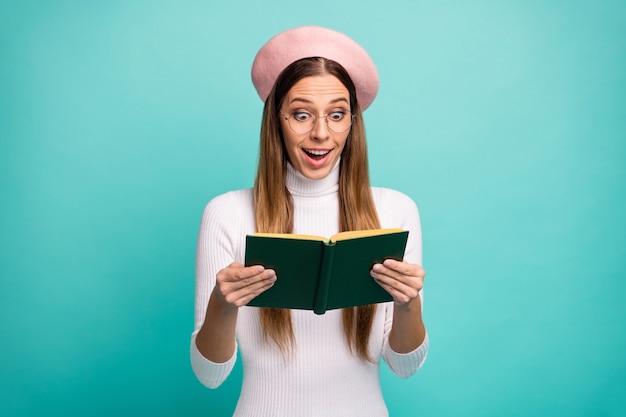 Photo d'une étudiante séduisante tenir un livre d'histoires d'amour roman intrigue intéressante bouche ouverte inattendue usure finale spécifications béret rose moderne col roulé blanc isolé fond de couleur sarcelle lumineux