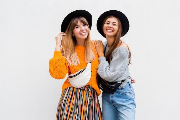 Photo extérieure de deux amies joyeuses passer du bon temps ensemble posant sur blanc