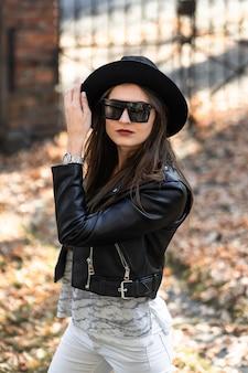 Photo extérieure d'une femme brune posant sur fond d'arbre en journée d'automne. portrait de style de rue de mode. fille portant un pantalon blanc, un t-shirt, une veste en cuir noir, des lunettes de soleil et un chapeau noir. concept de mode.