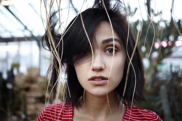 Photo extérieure de l'incroyable jeune femme brune d'apparence européenne regardant la caméra avec les lèvres séparées, ayant un regard pensif ou incertain, posant sur fond flou de la nature sauvage