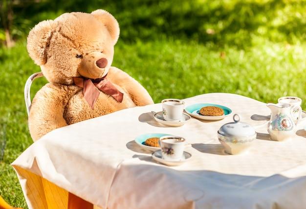 Photo extérieure d'un ours en peluche assis dans la cour et prenant son petit-déjeuner anglais