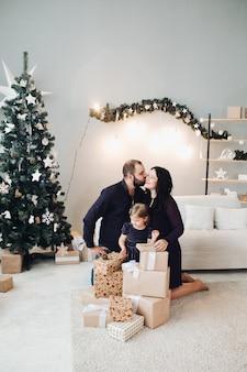 Photo de famille avec un enfant assis sur le canapé à côté de l'arbre de noël et se détend