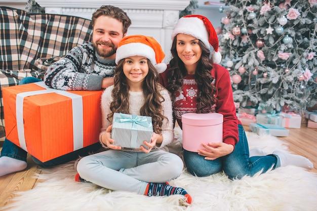Photo de famille heureuse, assis sur le sol et posant. chacun d'eux a une boîte avec un cadeau à l'intérieur. les gens portent des vêtements de fête.