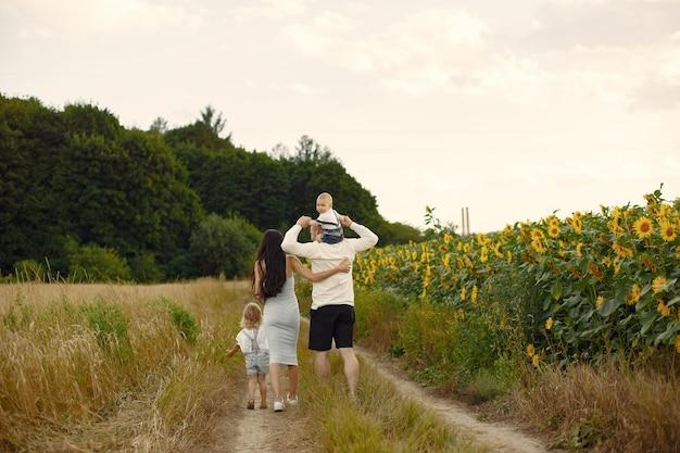 Photo de famille heureuse. parents et fille. famille ensemble dans le champ de tournesol. homme en chemise blanche.