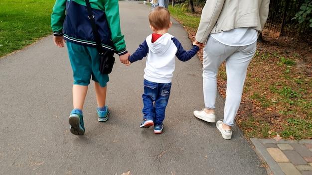 Photo de famille heureuse avec tout-petit garçon tenant par les mains et marchant dans le parc