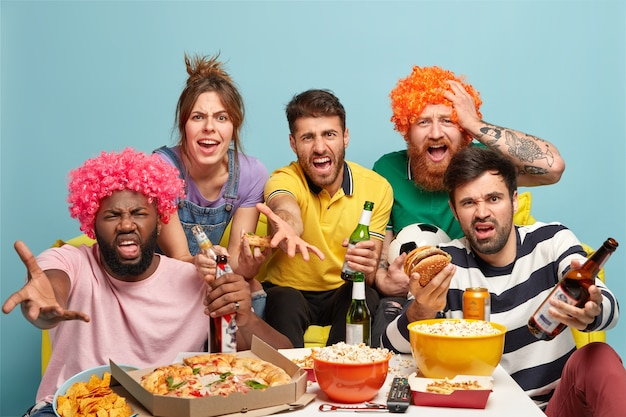 Photo de fans de football irrités insatisfaits du résultat du match, regarder la caméra avec colère, boire de la bière, manger de la pizza, hamburger, pop-corn