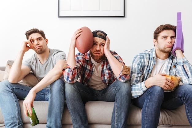 Photo de fans de sport masculins désespérés exprimant leur tristesse, tout en regardant un match de football à plat