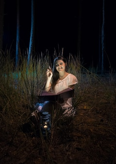 Photo fantastique d'une femme souriante tenant un livre dans la belle forêt de nuit