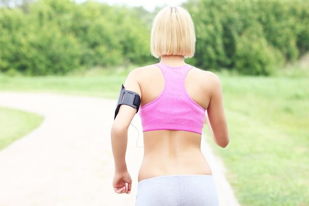 Une photo d'une femme active jogging dans le parc