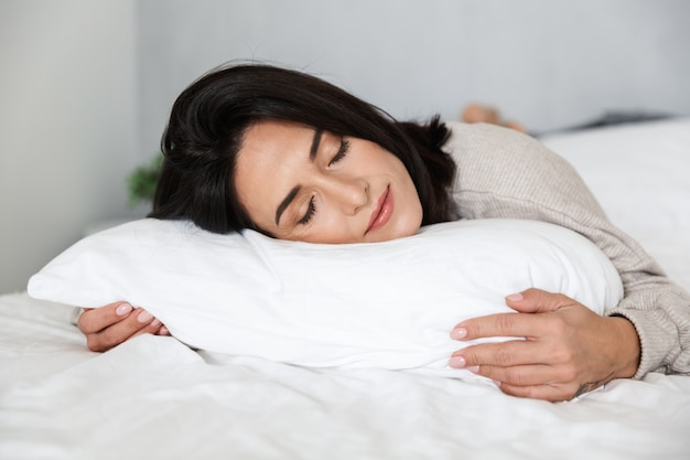 Photo d'une femme adulte de 30 ans dormir, allongé dans son lit avec des draps blancs à la maison