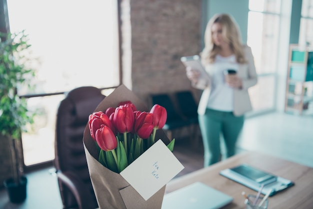 Photo de femme d'affaires blonde bouquet de tulipes rouges fraîches