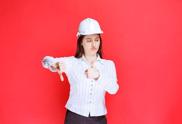 Photo d'une femme d'affaires en chapeau de sécurité montrant les pouces vers le bas et vers le haut.