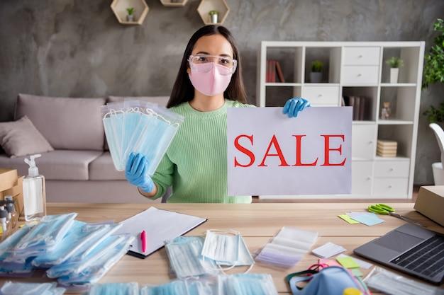 Photo d'une femme d'affaires chinoise faire une image blog internet lieu de travail tenir la main proposition de vente pancarte commande grippe faciale masques froids livraison gratuite bureau à domicile quarantaine à l'intérieur