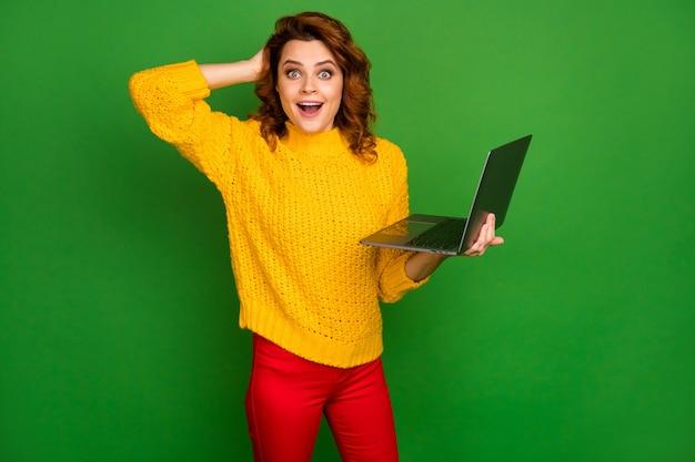 Photo de femme d'affaires drôle administrateur tenir les mains de l'ordinateur portable navigation sur le site web informatique bras sur la tête lire cool bonnes nouvelles porter jaune pull en tricot pantalon rouge isolé mur de couleur verte