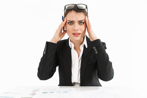 Photo d'une femme d'affaires frustrée vêtue de vêtements de cérémonie touchant sa tête tout en travaillant et assise au bureau dans un bureau isolé sur un mur blanc
