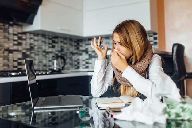 Photo d'une femme d'affaires inquiète tenant des serviettes à la main dans la cuisine à domicile et utilisant un ordinateur portable