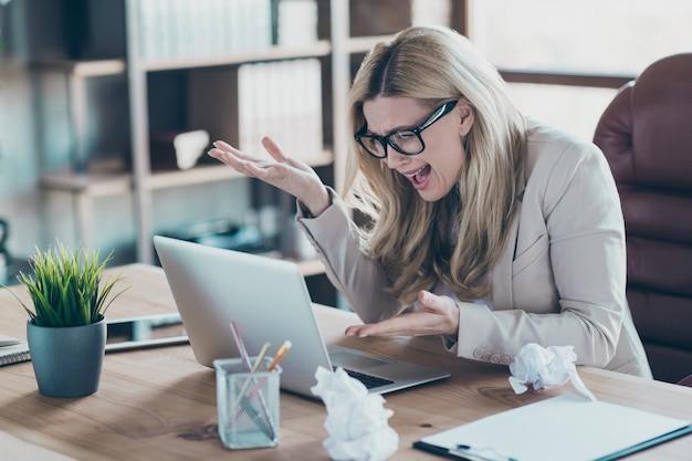 Photo de femme d'affaires à la recherche de netbook regardant l'écran crier des problèmes