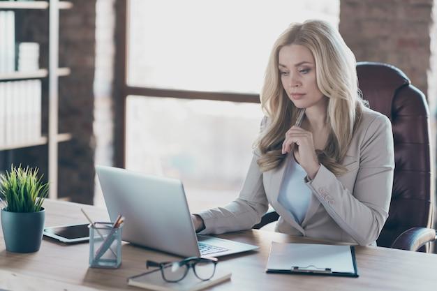 Photo de femme d'affaires à sérieusement ordinateur portable sur table pense