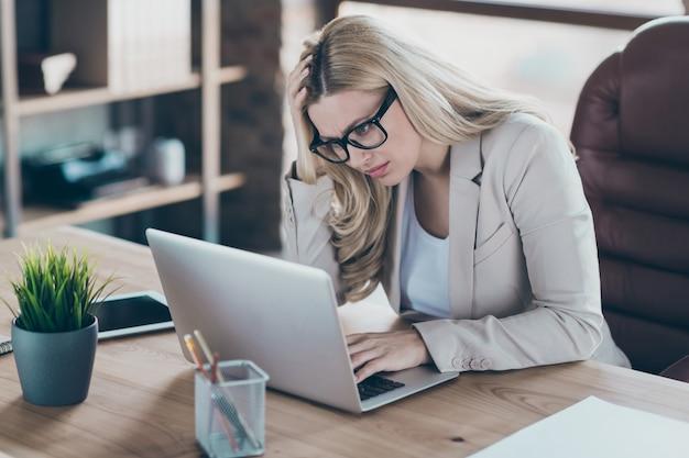 Photo de femme d'affaires à la table de l'ordinateur portable regardant le rapport en ligne surchargé de travail
