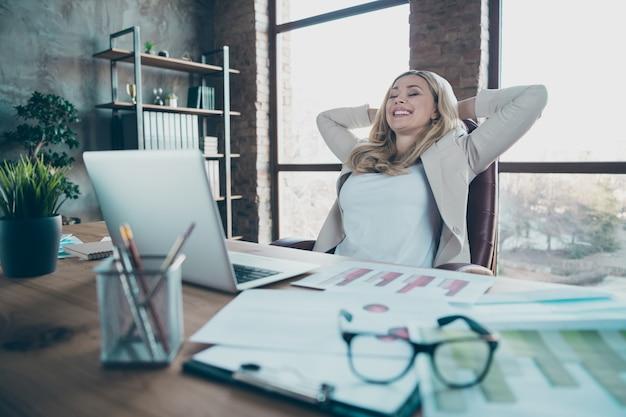 Photo de femme d'affaires table de travail netbook tenant la main derrière la tête se détendre