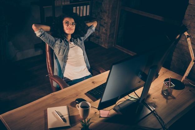 Photo de femme d'affaires travaillant des heures supplémentaires les mains derrière la tête rêve