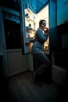 Photo d'une femme affamée mangeant la nuit près du réfrigérateur