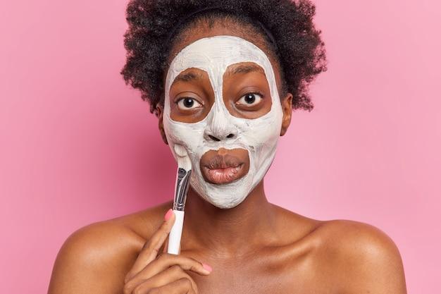 La photo d'une femme afro-américaine aux cheveux bouclés applique un masque facial nourrissant avec une brosse cosmétique subit des procédures de beauté se tient les épaules nues contre le mur rose a une peau lisse et saine