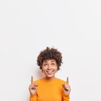 La photo d'une femme afro-américaine gaie pointe les doigts vers le haut, le texte promotionnel suggère de vérifier l'offre impressionnante qui montre une bannière d'espace de copie contre un mur blanc portant un pull décontracté.