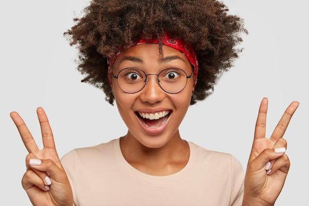 Photo d'une femme afro-américaine heureuse montre la victoire ou le signe de la paix
