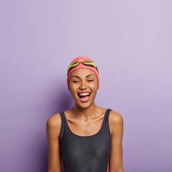 Photo de femme afro insouciante détendue avec un sourire à pleines dents, se sent ravie