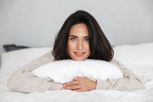 Photo d'une femme d'âge moyen de 30 ans souriant, allongé dans son lit avec des draps blancs à la maison