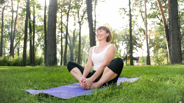 Photo d'une femme d'âge moyen en vêtements de sport pratiquant le yoga à l'extérieur au parc. femme d'âge moyen s'étirant et méditant à forest