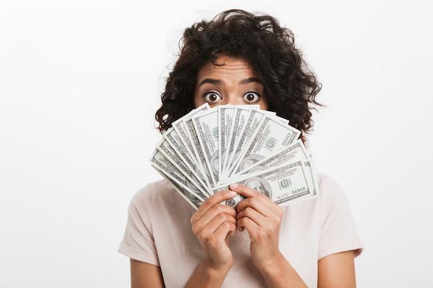 Photo d'une femme américaine surprise avec une coiffure afro couvrant le visage avec un ventilateur de billets d'un dollar d'argent et, isolé sur un mur blanc