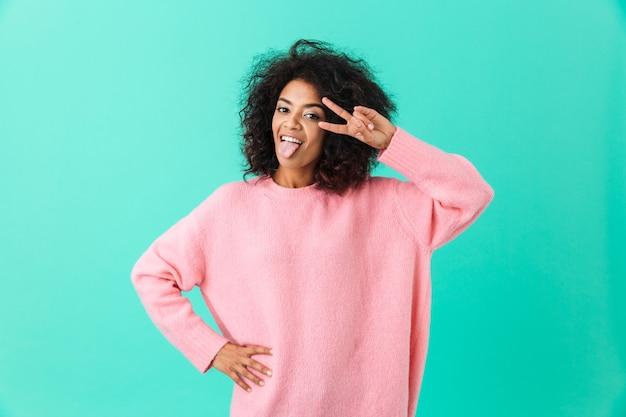 Photo de femme amusante en chemise rose qui sort la langue et montrant le signe de la victoire, isolé sur mur bleu